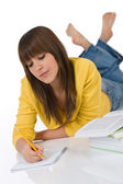 Student - female teenager write homework with book — Stock Photo