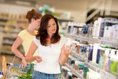 Shopping series - Brown hair woman in cosmetics department — Stock Photo