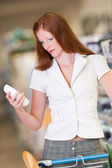 Shopping series - Red hair woman holding shampoo — Stock Photo