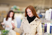 Series - mujer de pelo rojo sostiene desodorante de compras — Foto de Stock
