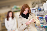 Shopping series - Red hair woman buying deodorant — Stock Photo