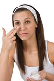 Beauty facial care - Young woman apply moisturizer — Stock Photo