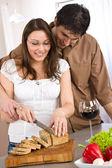 Happy couple cut bread in modern kitchen — Stock Photo