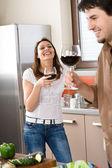 Jeune couple boire du vin rouge dans la cuisine moderne — Photo