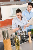 Young happy couple cooking in kitchen — Stock Photo