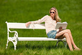 Spring - Young woman relaxing on bench in meadow — Stock Photo