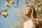 Spring - Young woman under blossom tree enjoy sun — Stock Photo