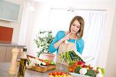 Gotowanie - kobieta czytająca książkę kucharską w kuchni — Zdjęcie stockowe