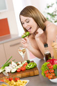 Cooking - happy woman biting slice of green pepper — Stock Photo