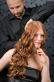 Professional hairdresser with fashion model at luxury salon — Stock Photo
