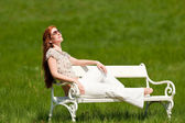 Red hair woman relaxing on white bench in spring — Stock Photo