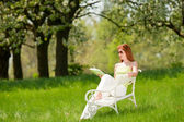 Young woman relaxing under blossom tree in spring — ストック写真