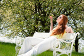 Young woman relaxing under blossom tree in spring — Foto de Stock
