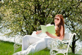 Young woman relaxing under blossom tree in spring — Stok fotoğraf