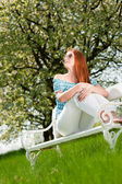 Young woman relaxing under blossom tree in spring — Stock fotografie
