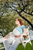 Young woman relaxing under blossom tree in spring — Stockfoto