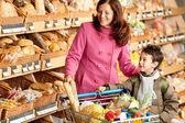 Sklep spożywczy, zakupy - uśmiechnięta kobieta z dzieckiem — Zdjęcie stockowe