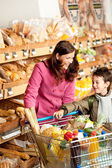 Grocery store shopping - Woman with child in winter outfit — Stock Photo