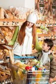 Grocery store shopping - Red hair woman with child — Stock Photo