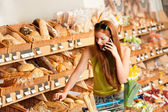 продуктовый магазин: красные волосы женщина с мобильного телефона — Стоковое фото