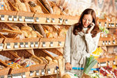 Grocery store: Young brown hair woman with mobile phone — Stock Photo