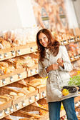 Grocery store: Young woman in bakery department — Stock Photo