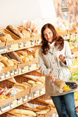 Grocery store: Young woman with shopping basket — Foto de Stock
