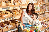 Grocery store shopping - Woman with child in a supermarket — Stock Photo