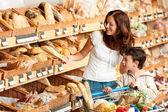 Supermercado compras - mujer de cabello castaño con el niño — Foto de Stock
