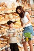 Obchod s potravinami nakupování - matka s dítětem kupovat chleba — Stock fotografie