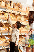 Grocery store shopping - Woman and child choosing bread — Stock Photo