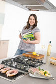 Cook - plus size woman grill fish in kitchen — Stock Photo
