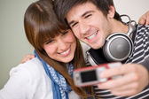 Students - happy teenage couple taking photo with camera — Stock Photo