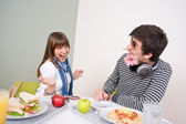 Student cafeteria - teenage couple having fun during lunch break — Stock Photo