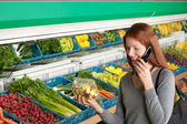 Grocery store shopping - Red hair woman with mobile phone — Stock Photo