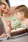 Mother and child tasting chocolate cake in kitchen — Stock Photo