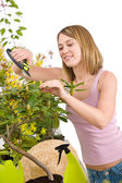 Gardening - Happy woman cutting Rhododendron flower — Stock Photo