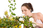 Portrait of woman smelling blossom of Rhododendron flower — Stock Photo