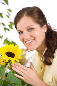 Portrait of happy woman with sunflower — Stock Photo