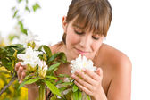 Portrait of woman smelling blossom of Rhododendron — Stock Photo
