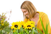 Gardening - portrait of smiling woman with sunflowers — Stock Photo