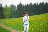 Jogging - sportive woman running in park with dandelion — Stock Photo