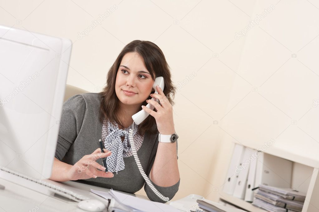 Young woman talking on the phone at office by computer — Stock Photo #4680197