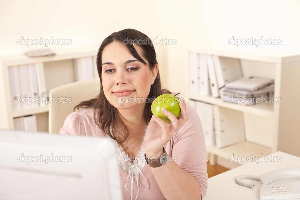 Young happy businesswoman holding apple at office having snack  Stock Photo #4680269