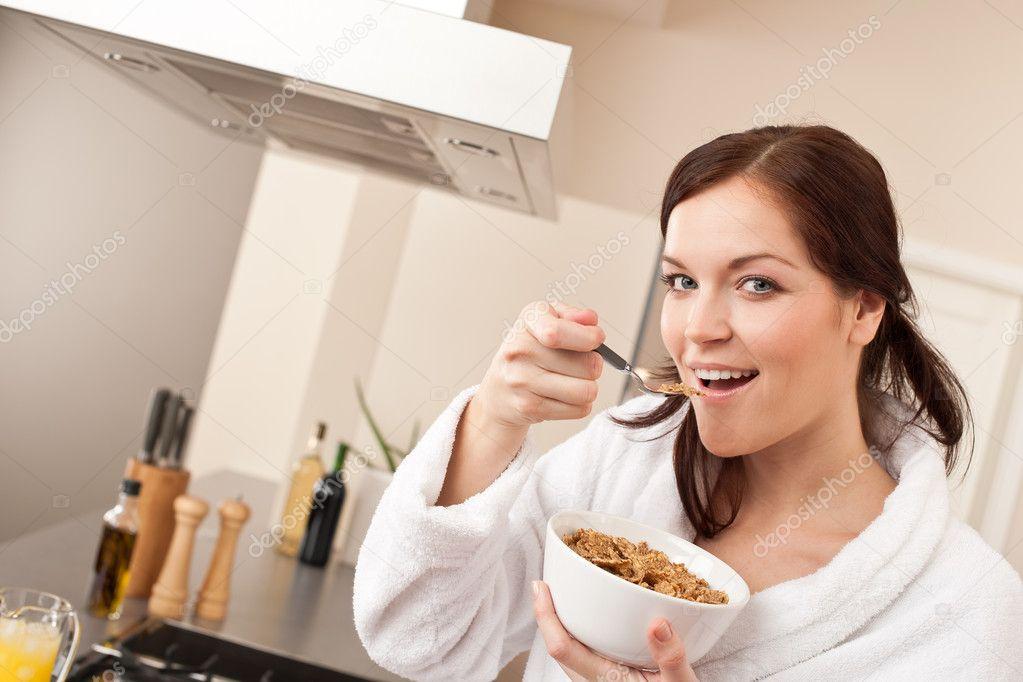 Glückliche Frau essen Müsli zum Frühstück in der Küche