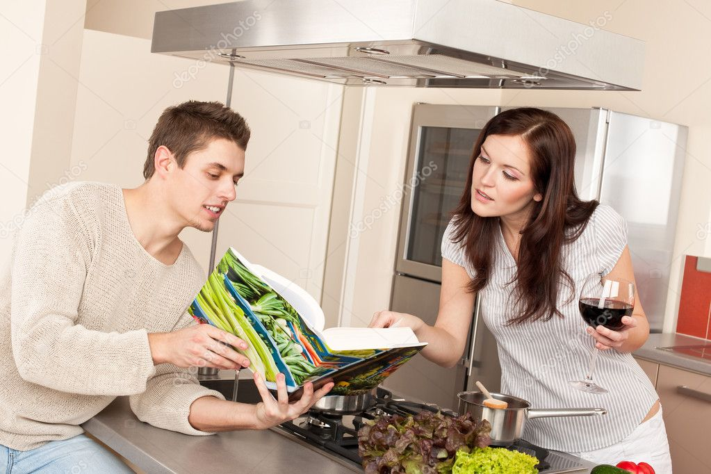 Young couple in kitchen choosing recipe from cookbook drinking red wine — Stock Photo #4680402