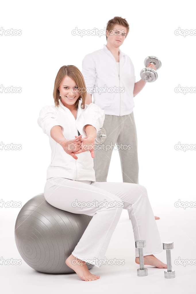 Young healthy couple training with weights and fitness ball on white — Stock Photo #4680483