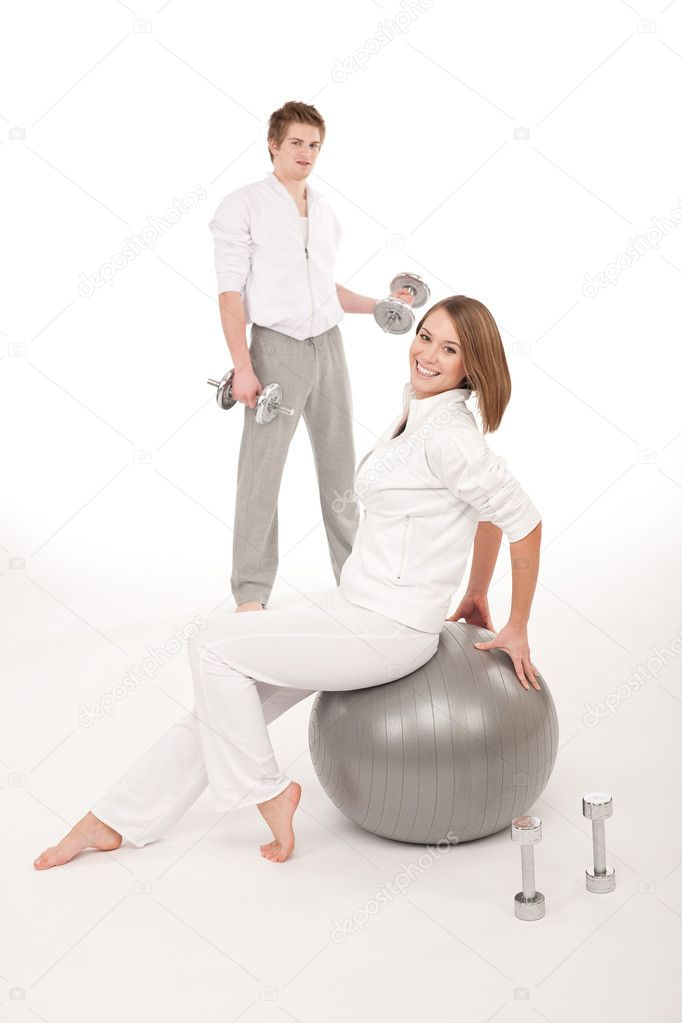 Young healthy couple training with weights and fitness ball on white  Stock Photo #4680489