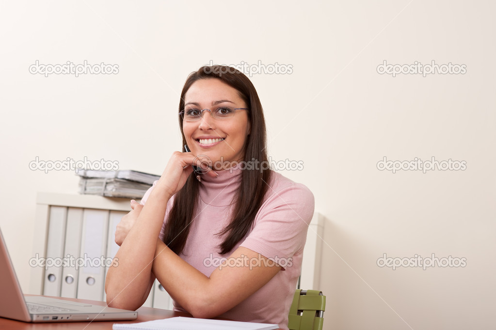 Smiling businesswoman with laptop sitting at office — Stock Photo #4681848