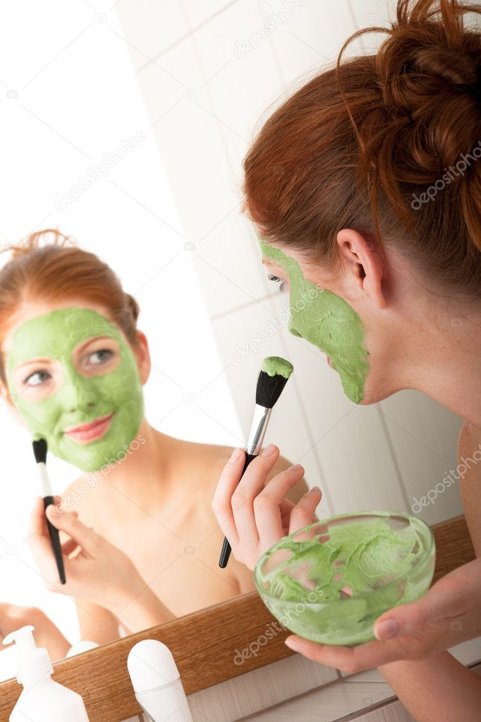 Young woman applying green facial mask in the bathroom — Stock Photo #4682006